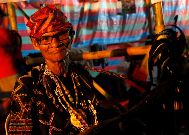 A Lumad wearing their traditional garb and carrying a traditional instrument.