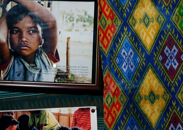 Details of a traditional Lumad cloth is seen beside a framed photograph of a Lumad boy.